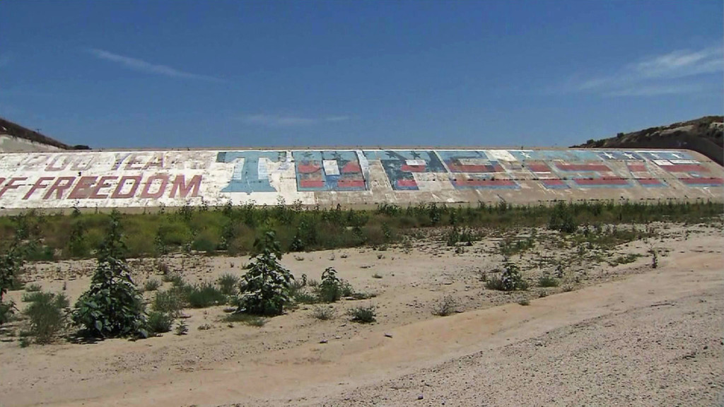 A now-faded and defaced bicentennial mural painted on the Prado Dam spillway in Corona, California